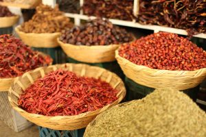 Image of different bowls of spices in a spice market.